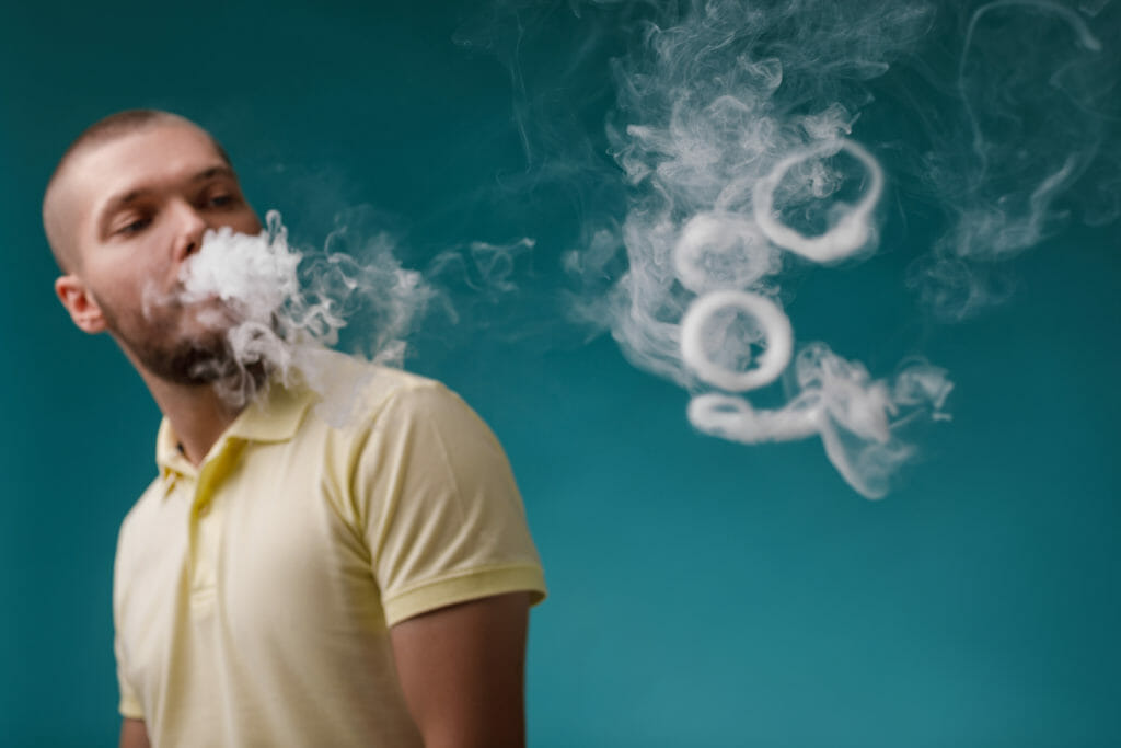 vaping man smoking e-cigarette. Guy launches ring of white smoke. focus on smoke