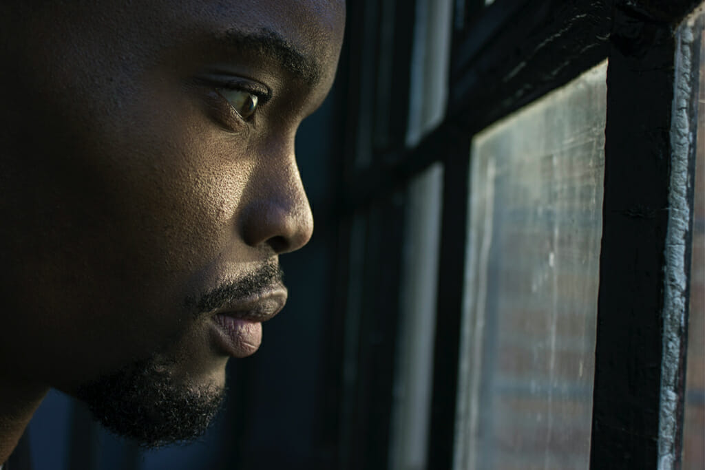 Man with a worried look, possibly as a result of substance abuse depression, peering out a window