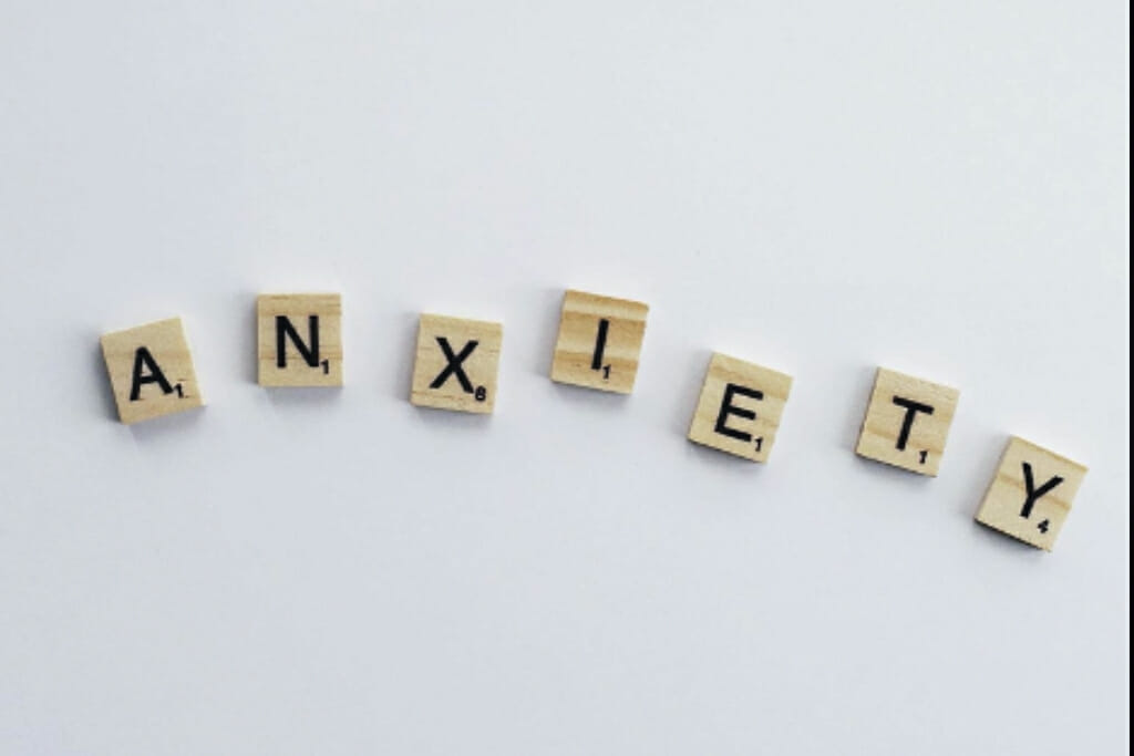 "Wooden Scrabble® tiles with a black letter in each, spelling the word ""anxiety""."