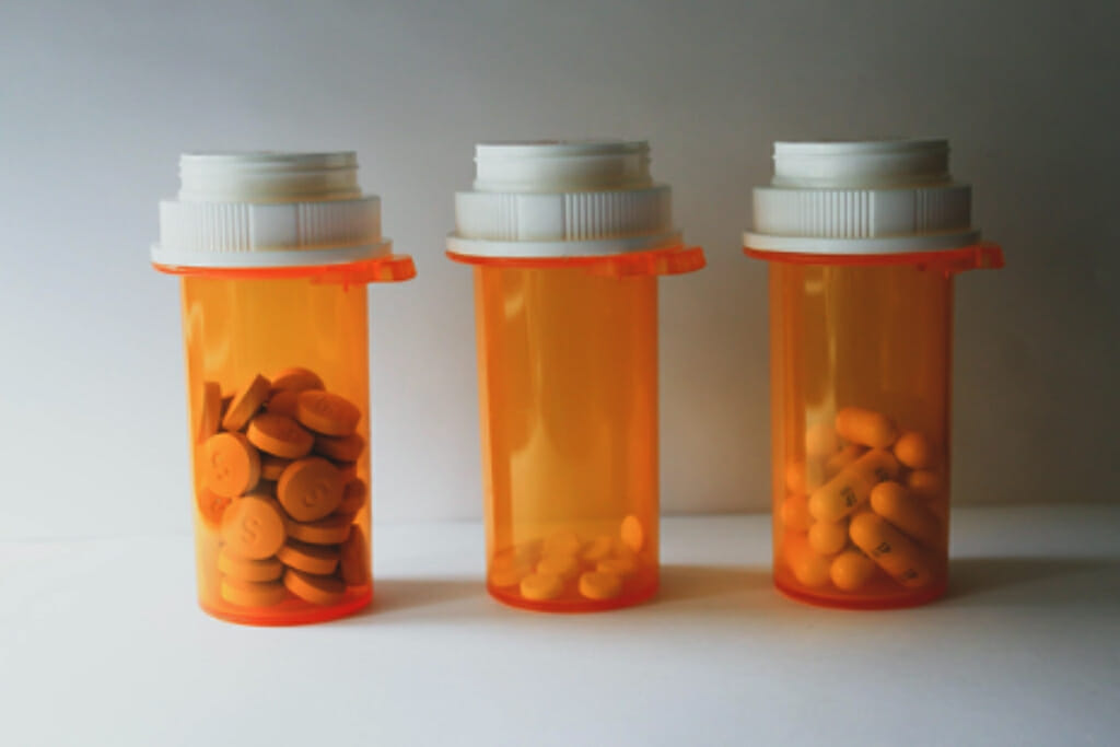 Three orange pill bottles filled with differently shaped pills.