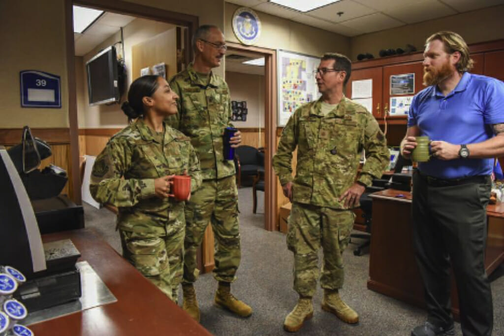 Four active-duty service members taking a moment to have a coffee with one another in an office setting.