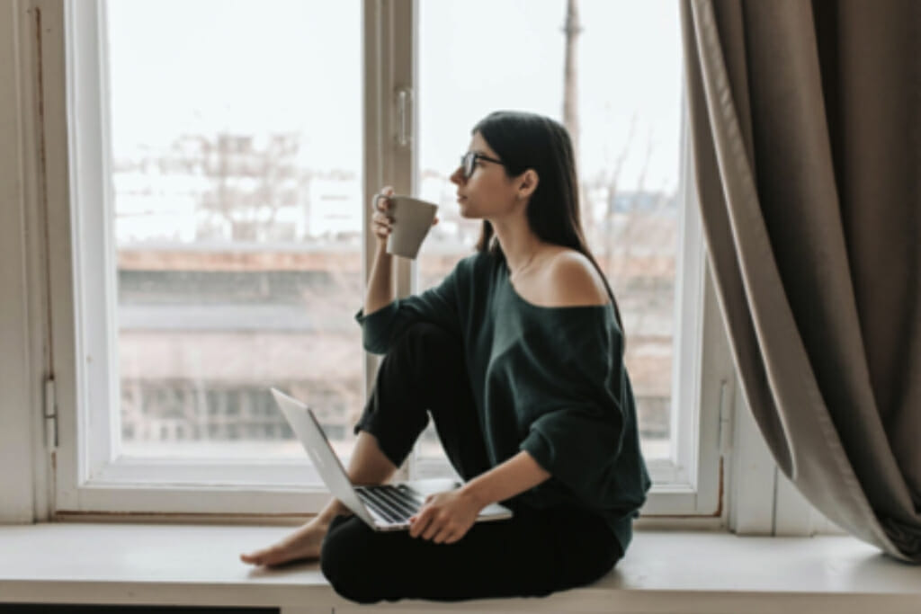 A woman drinking coffee and holding a laptop, while seated on a windowsill with the curtains opened to let daylight in.